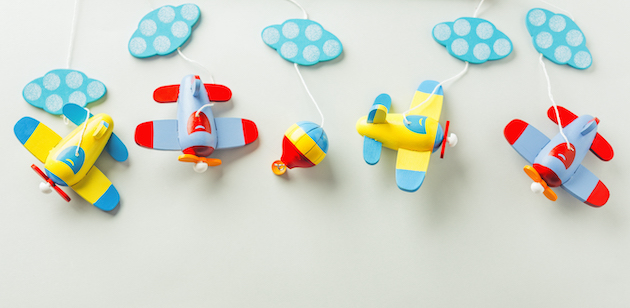 Baby care or baby shower concept. Flat Lay. Wooden planes on pastel background. Baby boy concept.