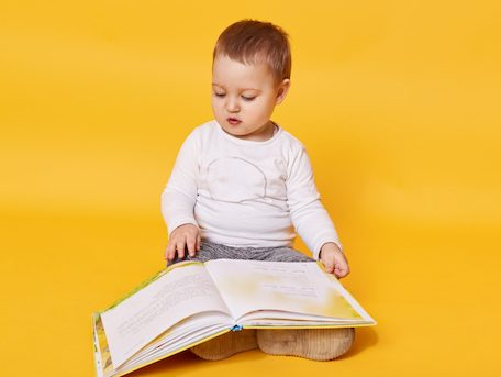 Toddler girl pretends to read book while sitting on floor, viewing pictures and turning pages, little girl looks concentrated, wearing casual white shirt, posing isolated over yellow background.